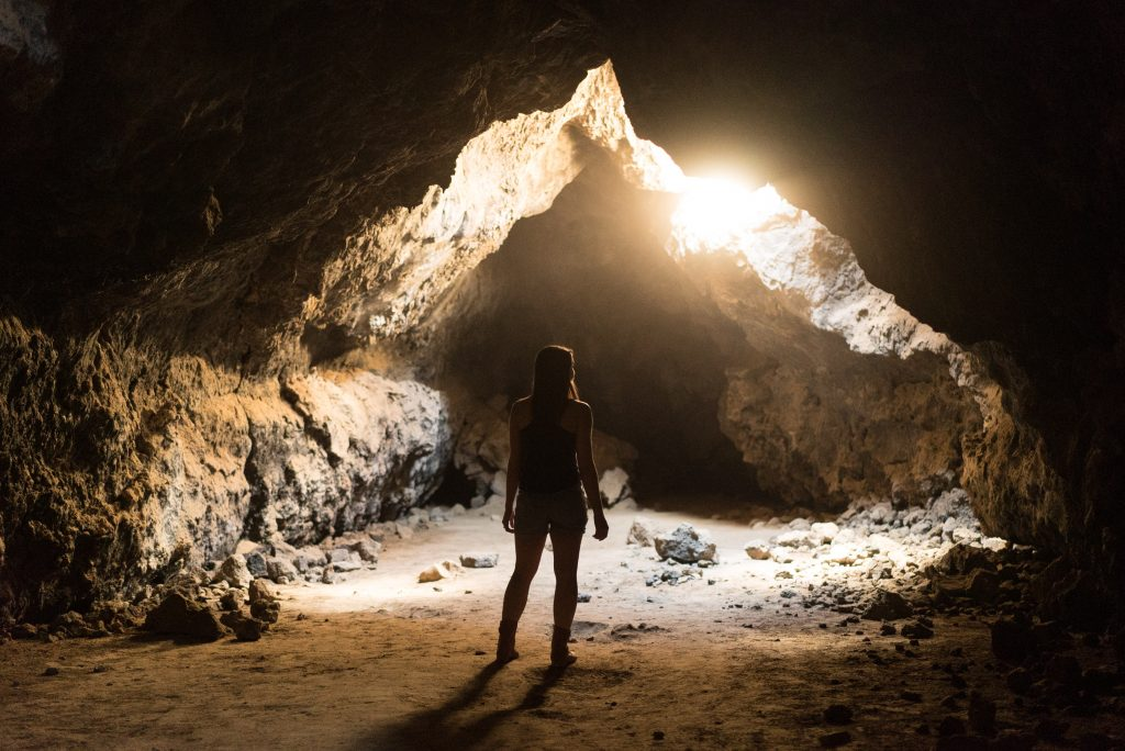 Woman standing in cave with light shining in